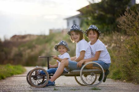 Happy children, boy brothers, riding old retro car with four wheels in a village