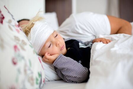 Little toddler boy with head injury, lying in bed, tired, sleeping Imagens