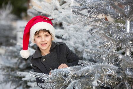 Sweet child on Christmas with santa hat, having fun outdoors, smiling happily