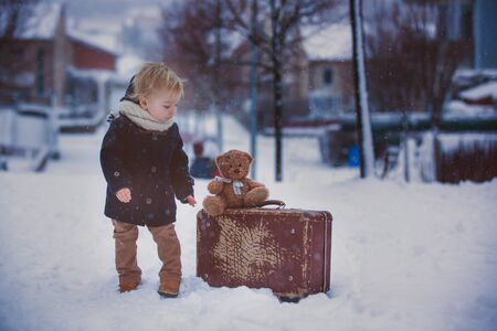 Baby playing with teddy in the snow, winter time. Little toddler boy in blue coat, holding suitcase and teddy bear, playing outdoors in winter park. Children play in snowy park Imagens