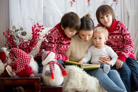 Mother reads book to her sons, children sitting in cozy armchair on a snowy winter day, wintertime