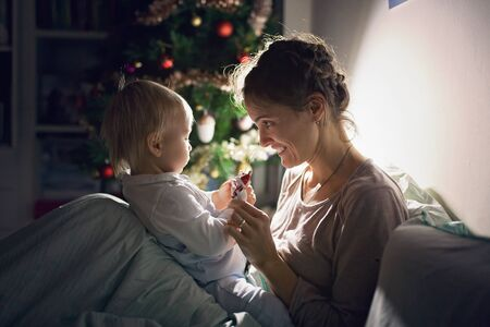 Young beautiful mother, breastfeeding her newborn baby boy at night, dim light. Mom breastfeeding toddler on Christmas