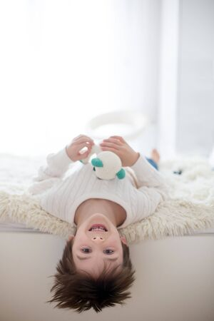 Cute portrait of child upside down, lying on bed, smiling at camera and playing with toy