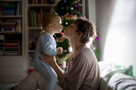 Young beautiful mother, kissing her toddler baby boy at night, dim light. Mom breastfeeding toddler on Christmas