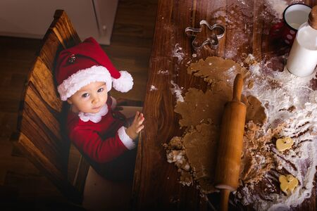 Sweet toddler child, boy, helping mommy preparing Christmas cookies at home in kitchen Stockfoto