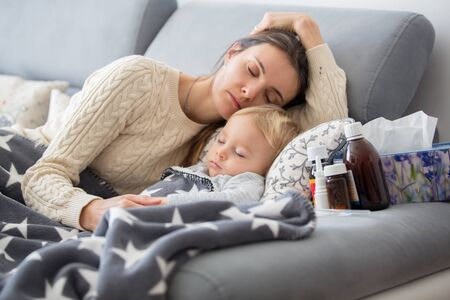 Sick child, toddler boy lying on the couch in living room with a fever, mom cheching his temperature, resting at home