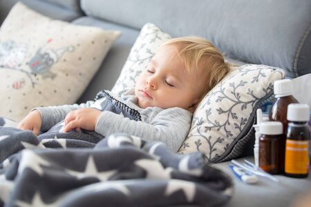 Sick child, toddler boy lying on the couch in living room with a fever, resting at home