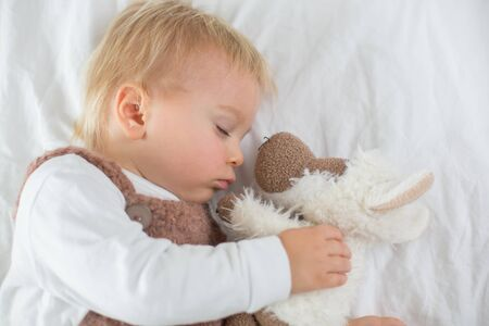 Sweet baby boy in cute overall, sleeping in bed with teddy bear stuffed toys, winter landscape behind him 写真素材