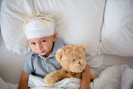 Little toddler boy with head injury, lying in bed, tired, sleeping Stockfoto
