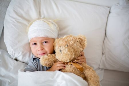 Little toddler boy with head injury, lying in bed, tired, sleeping 写真素材