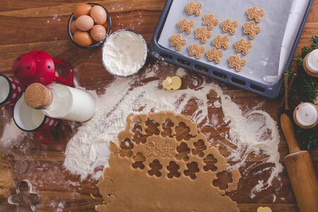 Homemade cookies, ready to bake, dough lying on the table, cutter in shape of gingerman