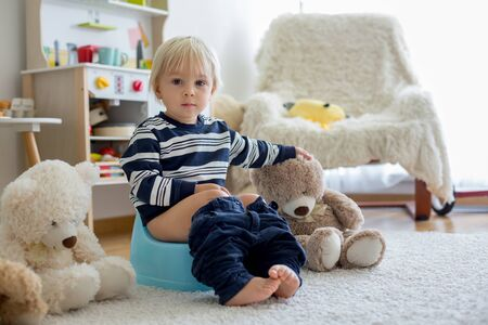 Cute toddler boy, potty training, playing with his teddy bear on potty