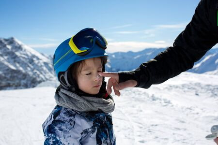 Parent, father, putting sun cream on child's face on top of mountain, preparing him for a sunny day of skiing Stock Photo