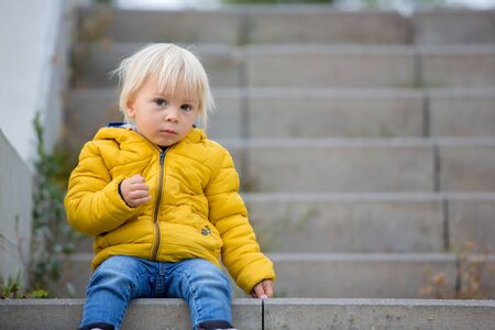 Blonde little toddler child in yellow jacket, playing on the playground, autumn sunny day Stock Photo