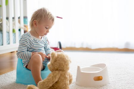 Cute toddler boy, potty training, playing with his teddy bear on potty Stock Photo