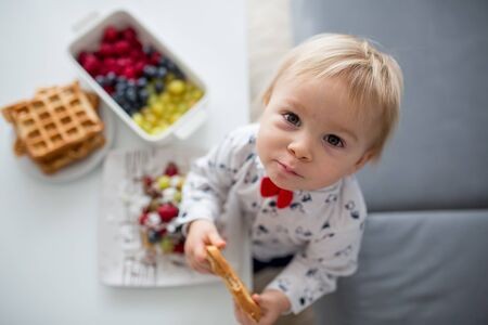 Sweet toddler birthday boy, eating belgian waffle with raspberries, blueberries, cocnut and chocolate at home Фото со стока