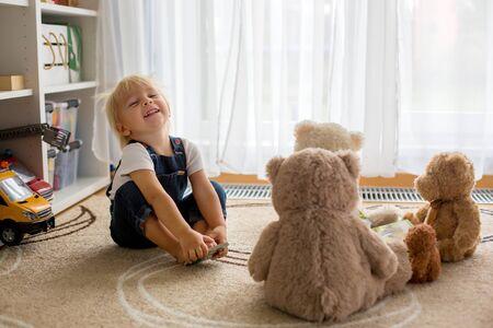 Niño pequeño, leyendo un libro a sus amigos osos de peluche en casa, sentado en la sala de estar