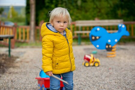 Blonde little toddler child in yellow jacket, playing on the playground, autumn sunny day