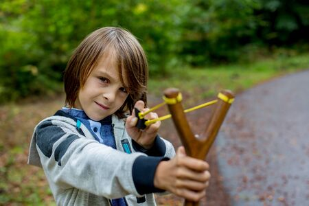 Preschool boy, child with slingshot in fores, shooting at target in the woods 写真素材