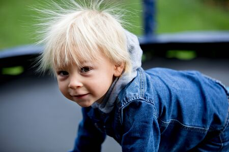 Cute little boy with static electricy hair, having his funny portrait taken outdoors on a trampoline Stock Photo