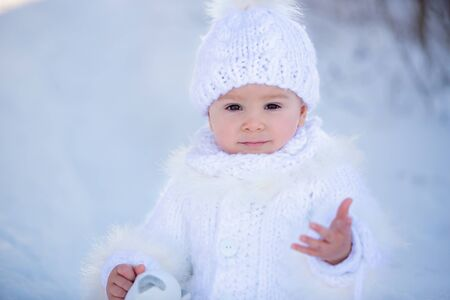 Baby playing with teddy in the snow, winter time. Little toddler boy in handmade white snowsuit, holding teddy bear on sunset, playing outdoors in winter park. Children play in snowy park