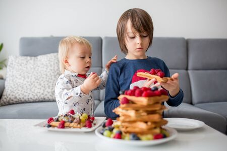 Sweet toddler birthday boy and his brothers, eating Belgian waffle with raspberries, blueberries, coconut and chocolate for breakfast at home Фото со стока