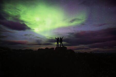 Happy family, observing the sky in Iceland, watching nortern lights on a clear sky night. Aurora borealis in Iceland autumn time Banco de Imagens - 131292575