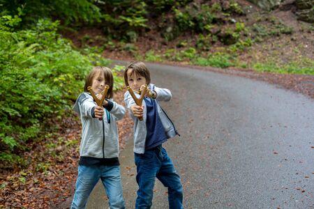 Niño en edad preescolar, niño con tirachinas en fores, disparando al blanco en el bosque