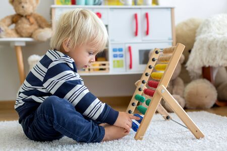 Cute toddler boy, playing with counter, colorful abacus, child learning counting alone at home