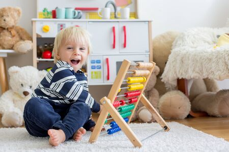 Cute toddler boy, playing with counter, colorful abacus, child learning counting alone at home 写真素材 - 131548053