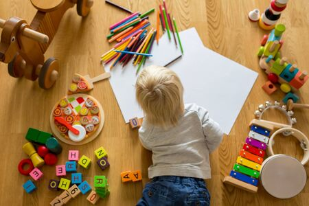 Little blonde toddler boy, drawing with pastels and coloring pens, playing with early development wooden toys