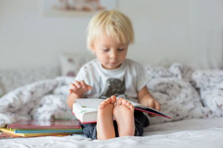 Sweet toddler boy, reading book at home, sitting in bed, lots of books around him