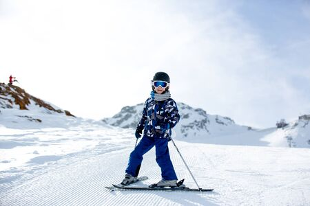 Happy people, children and adults, skiing on a sunny day in Tyrol mountains. Kids having fun while skiing Stock Photo