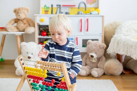 Cute toddler boy, playing with counter, colorful abacus, child learning counting alone at home 写真素材 - 131548326