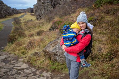 Young mother holding sleeping baby on a path in scenic Thingvellir National Park rift valley, Iceland autumntime