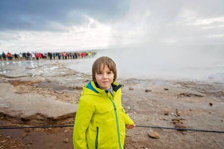 Children, enjoying the eruption of Strokkur Geysir in Iceland autumntime