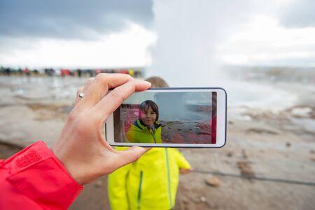 Mother recording video of her preschool son, boy enjoying the eruption of Strokkur Geysir in Iceland autumntime Reklamní fotografie