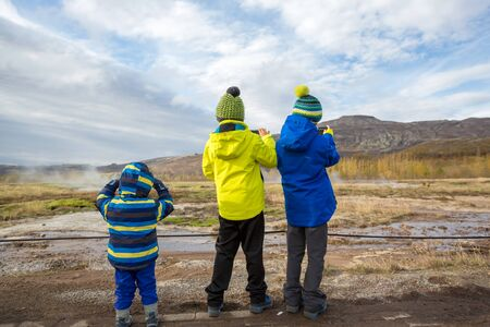 Children, taking picture of Strokkur Geysir while erupting, Iceland autumntime Archivio Fotografico