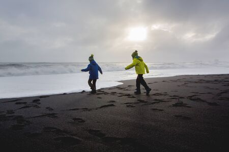 Children running from and to the ocean in black sand beach of Reynisfjara and the mount Reynisfjall in Iceland on a cold winter rainy day