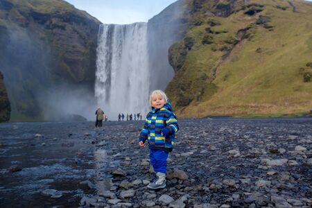 Toddler boy, playing with rocks on the river in fronf of Skogafoss waterfall in Iceland on a sunset cloudy day, autumntime