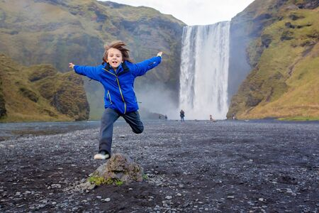 Cute child running in front of the Skogafoss waterfall in Iceland on a sunset cloudy day, autumntime 写真素材