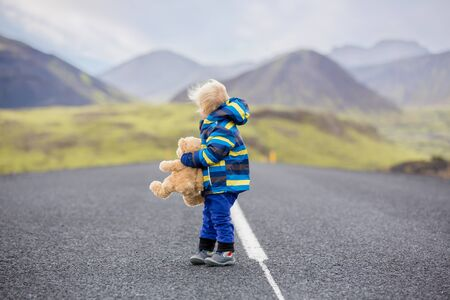 Cute toddler boy with teddy bear in hand, running on a road in Iceland on a rainy day