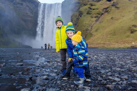 Toddler boy and siblings, playing with rocks on the river in fronf of Skogafoss waterfall in Iceland on a sunset cloudy day, autumntime 写真素材 - 132229011