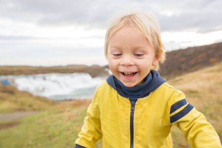 Portrait of a smiling baby boy near smaller waterfall around Gullfoss, Iceland autumntime