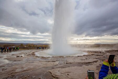 People taking pictures with cellphones of scenic Strokkur Geyser while erupting, Iceland autumntime