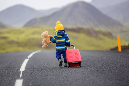 Cute toddler boy with teddy bearand suitcase in hand, running on a road in Iceland on a rainy day Stok Fotoğraf