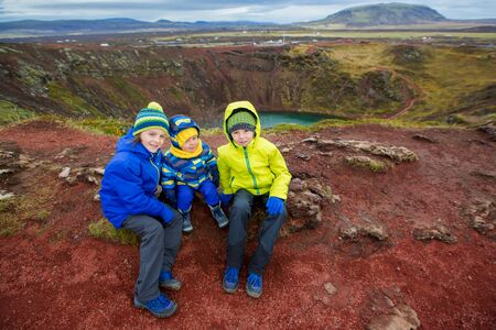 Children, boys, posing in front of Kerid crater lake in Iceland, autumntime Фото со стока