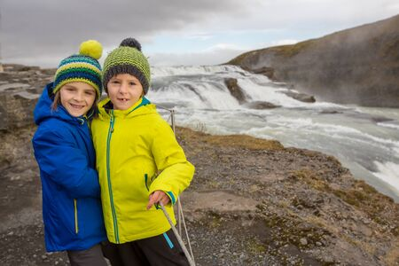 Children, enjoying the big majestic Gullfoss waterfall in mountains in Iceland, autumntime