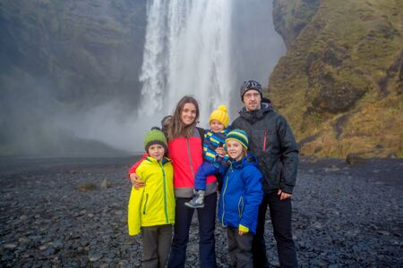 Happy family, posing in front of the Skogafoss waterfall in Iceland on a sunset cloudy day, autumntime 写真素材 - 132230103