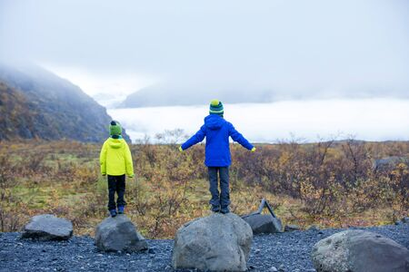 Children posing in beautiful aerial view of the nature in Skaftafell Glacier national park on a gorgeous autumn day in Iceland
